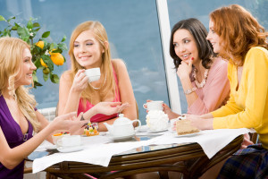 Portrait of four attractive women having lunch and discussing