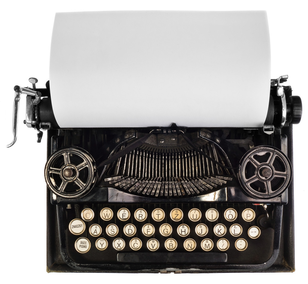 Old antique vintage portable typewriter with a blank sheet of paper. Antique typewriter in black with white keys of the Polish alphabet. The device isolated on a white background with light shadow and reflection.