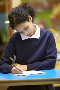 Female Elementary School Pupil Writing Book In Classroom