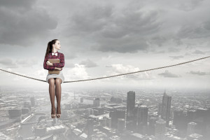 Young woman sitting on rope above city and reading book