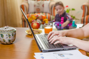 Detail of a woman hands writing in notebook and boy playing on the background. Home office concept.