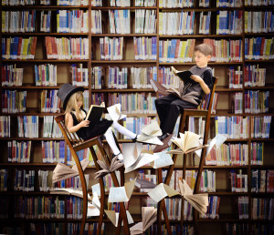 Two children are reading books on long surreal wooden chairs in a library with books and papers flying around them for an education or imagination concept.