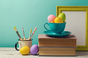 Easter holiday celebration with handmade painted eggs in coffee cup books and brushes. Creative workplace concept
