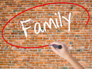 Woman Hand Writing Family with black marker on visual screen. Isolated on bricks. Business concept. Stock Photo