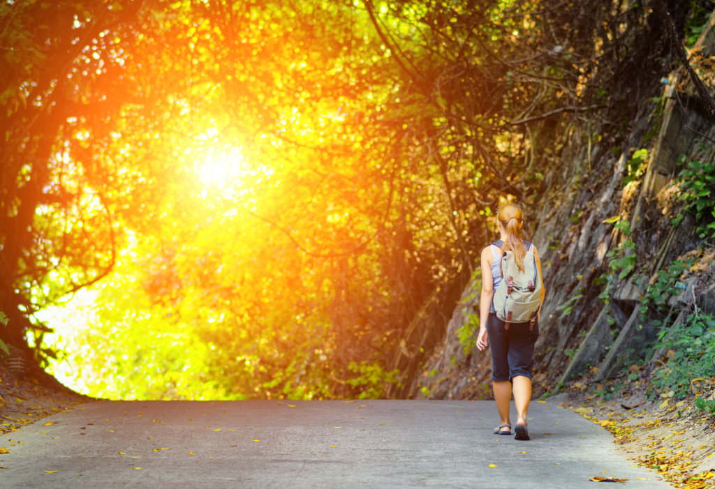 Young woman hiking with backpack. Girl walking on mysterious road through scenic green forest at sunset.